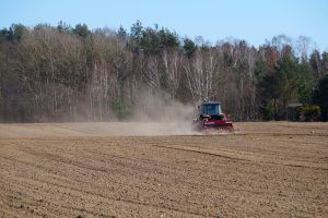The tractor harrows fields for cultivation. Spring field work.