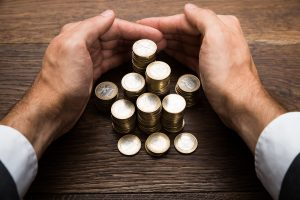 Businessman's Hand Protecting Euro Coins