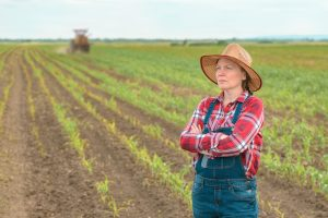 Worried female farmer standing in corn field and looking over cr