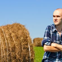 morning portrait of farmer in field against wheat bales